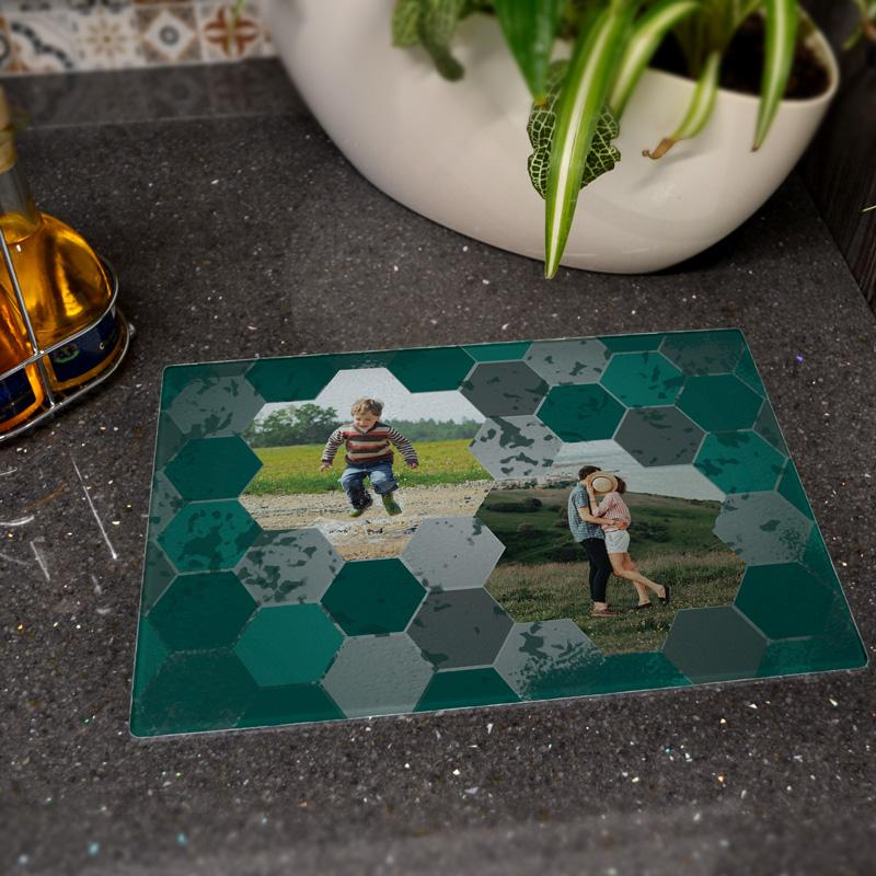 A personalised glass worktop saver with a teal hexagon pattern and family photos printed on it