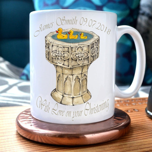 "A mug with a personalised design, the design includes a font with 3 rubber ducks swimming in it, and a message which reads ""James Smith 9/7/2018, with love on your christening"""