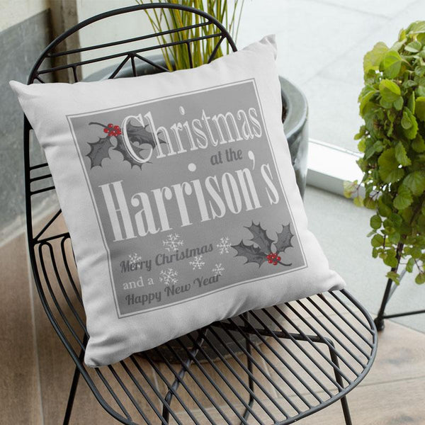 A personalised white and grey cushion with a Christmas design and a family name printed on it.