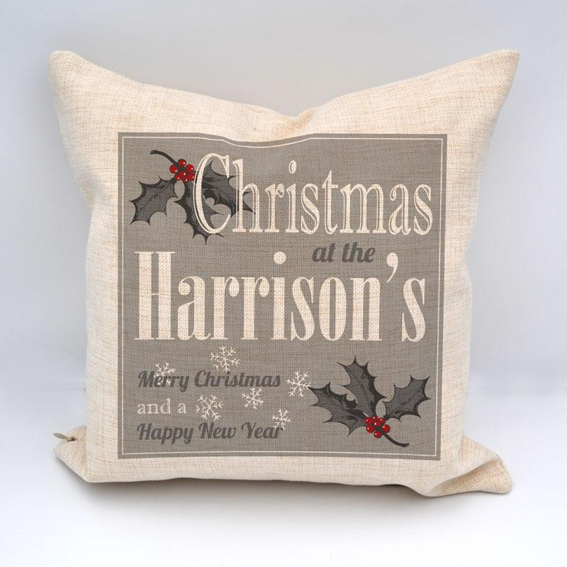 A personalised white and grey cushion with a Christmas design and a family name printed on it. The photo shows the 2 cover options, plain white and cream linen.