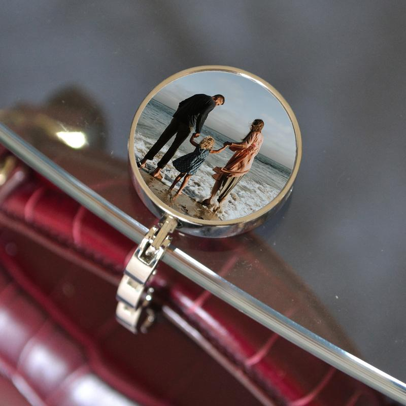 A personalised handbag hook with a photo printed in the centre