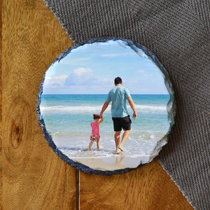 A personalised round photo slate coaster with a photo of a father and daughter at the beach printed on it.