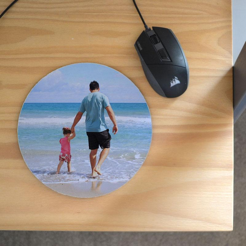 A personalised circular mouse mat with a family photo printed on it.