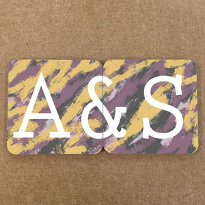 "A pair of personalised coasters with a couples initials on them. When the coasters are next to eachother the design is compleate and reads ""A&S"". The font is white and the background is a yellow and purple abstract pattern."