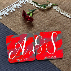 "a pair of personalised coasters with an abstract ruby red and grey background. The coasters are personalised with a couple's initials and when placed next to each other read ""A&S"""