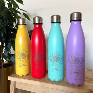 Personalised metal water bottles in a selection of bright colours. The bottles have a flower pattern and a name etched into the surface.