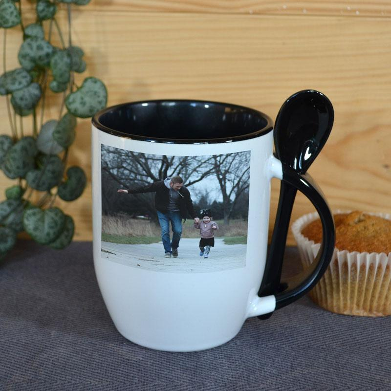 A personalised white mug with a photo printed on it. The mug has a black handle and a matching black spoon.