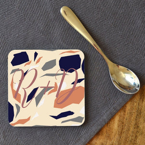 "A personalised square terrazzo coaster, the terrazzo pattern is cream, dark blue, pale grey and muted orange. The coaster is personalised with the initials ""R&D"" and the text is in dusky pink"