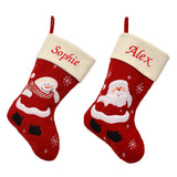 2 red and cream personalised Christmas stockings, one with a Santa picture and one with a snowman picture. The main section of the stockings is red, the top of the stockings is cream and embroidered with a name in red lettering.