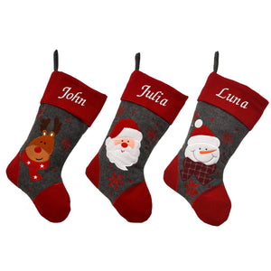An image of 3 personalised Christmas stockings, one with a reindeer, one with a Santa and one with a snowman. The designs are on a grey felt background and have a red felt top, heal and toe. The stockings are personalised with names which are embroidered in white on the top of the stocking.