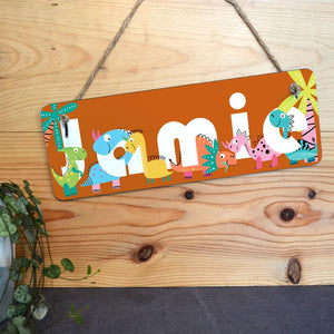 A personalised orange sign with dinosaurs printed on it and a name in white lettering.