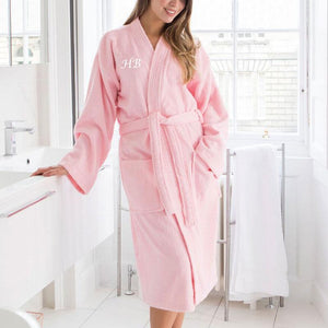 A personalised embroidered towelling robe in pale pink with white lettering