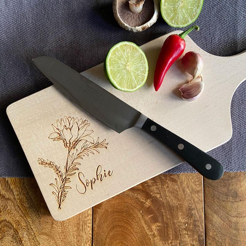 A personalised wooden chopping board with a name and flower pattern engraved on the surface