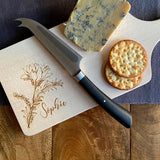 A personalised engraved wooden cheese board with a name and flower pattern