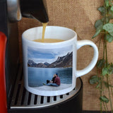 A personalised small coffee mug with a photo printed on it. The mug is on a coffee machine and is being filled with espresso.