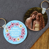 A personalised round keyring with flowers and a message on one side an a photo on the other side