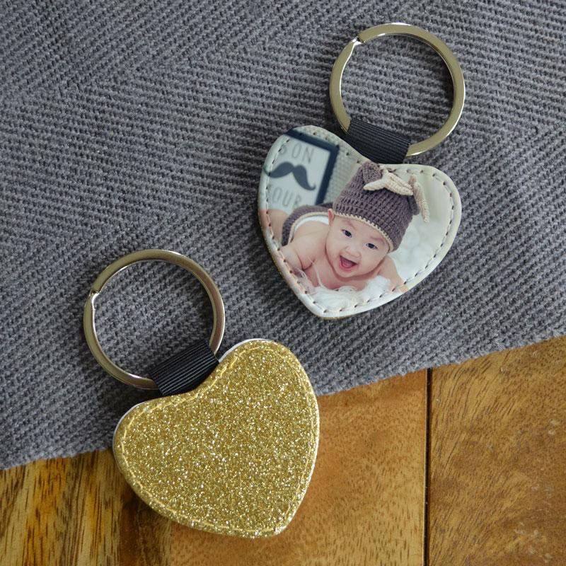 A personalised heart keyring with a photo of a baby on one side and gold glitter on the other side.