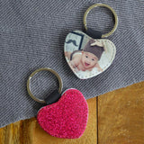A personalised heart keyring with a photo of a baby on one side and pink glitter on the other side.