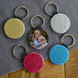 Personalised glitter keyring in pink, blue, gold and silver, the keyrings have a photo on one side and glitter on the other.