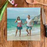 A personalised square glass chopping board with a photo of a man and a woman on holiday printed on it.