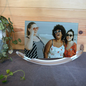 A personalised glass panel displayed on an acrylic base. The glass is printed with a photo of 3 friends.