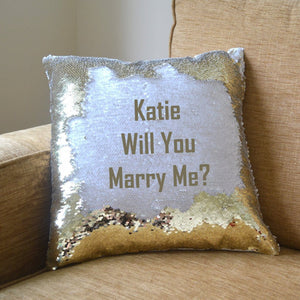 "A cushion covered in gold sequins with a hidden message reading ""Kate, will you marry me"""