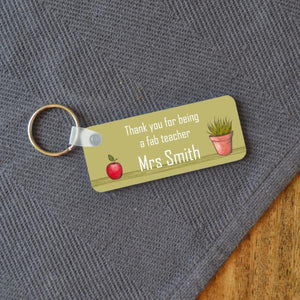 A green rectangular key ring personalised with a teachers name. The design includes an apple and a pot plant.