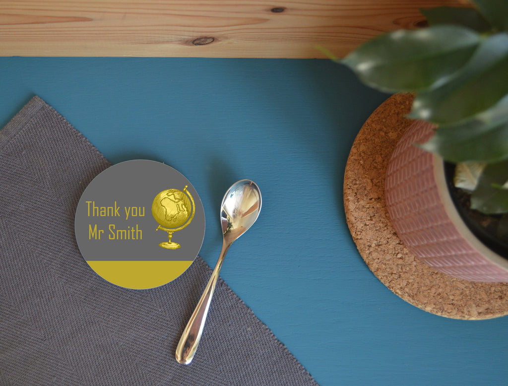 A yellow and grey personalised coaster on a blue table next to a pot plant.