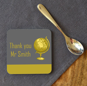 A personalised square coaster on a table next to a teaspoon. The design on the coaster is grey and yellow and includes a yellow globe.