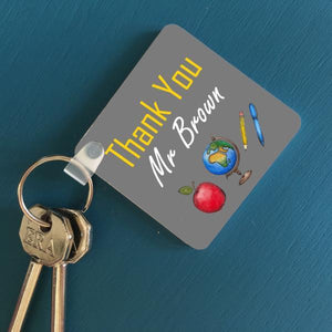 "An image of a personalised key ring on a blue table. The design on the keyring features an apple, a globe, a pen and a pencil. The message on the key ring reads ""thank you Mr Brown"""