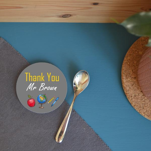 "A round coaster with a personalised design including a globe, an apple a pen and a pencil. The message reads ""thank you mr brown"". The coaster is on a blue table next to a pot plant."