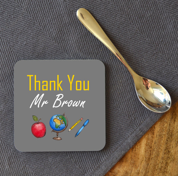 "A coaster on a table next to a teaspoon. The coaster has a personalised design which includes a globe, an apple, a pen and a pencil. The message on the design reads ""thank you Mr Brown"""