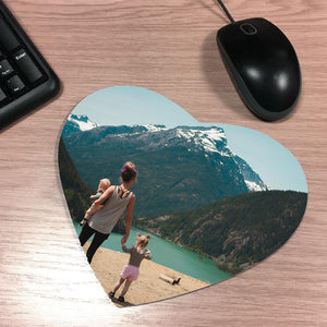 A personalised heart shaped mousemat with a photo printed on it