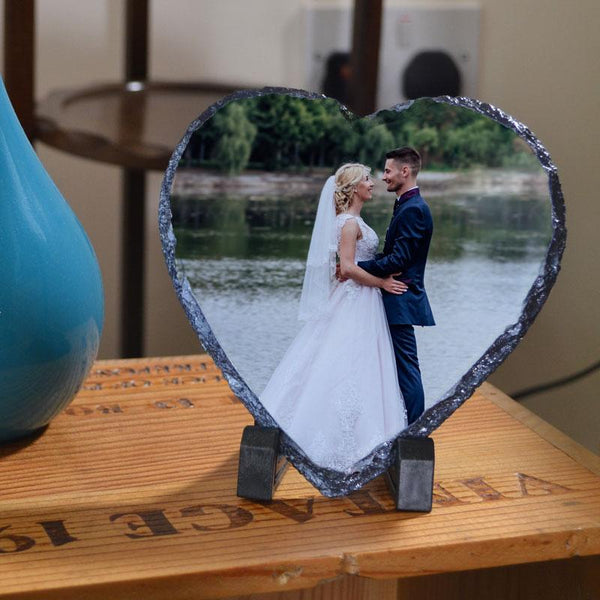 A personalised heart shaped slate plaque with a wedding photo printed on it.