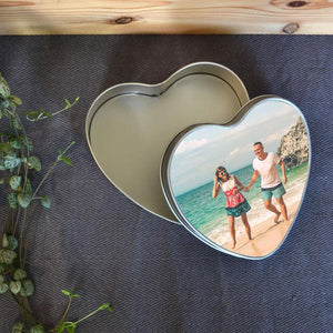 A personalised heart shaped metal tin with a holiday photo printed on the lid.