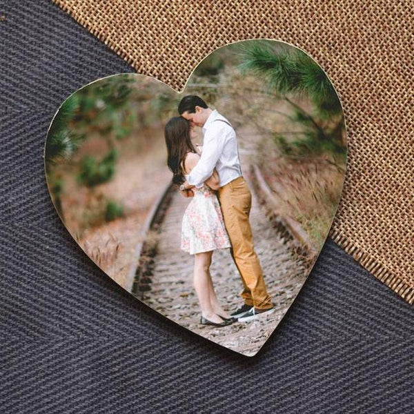 A personalised heart photo coaster with a photograph of a couple printed on it