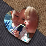 A personalised heart coaster with a photo of 2 children printed on it