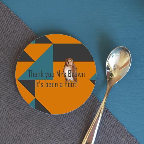 "A round coaster on a blue table next to a teaspoon and a pot plant. The design on the coaster has an orange, teal and grey background with an illustration of an owl and a message which reads ""thank you Mrs Brown, its been a hoot!"""