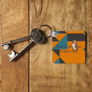 "A square key ring on a wooden table with 2 keys. The design on the key ring shows an orange, teal and grey background with an illustration of an owl and the message ""thank you Mrs Brown, its been a hoot!"""