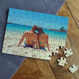 A personalised photo jigsaw puzzle with a photo of a couple on the beach printed on it.