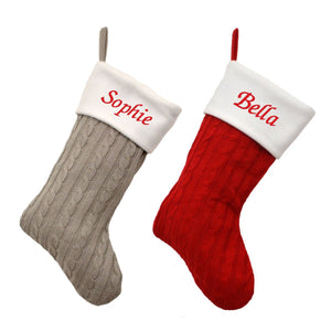 Two personalised Christmas stockings, one in grey and one in red. The stockings are made from a knitted fabric in a traditional pattern. The stockings have white felt tops with names embroidered in red text.
