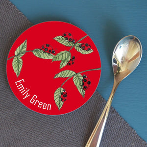 "A round coaster with an illustrated pattern of ladybirds on leaves, the background is red and the coaster includes the name ""Emily Green"""