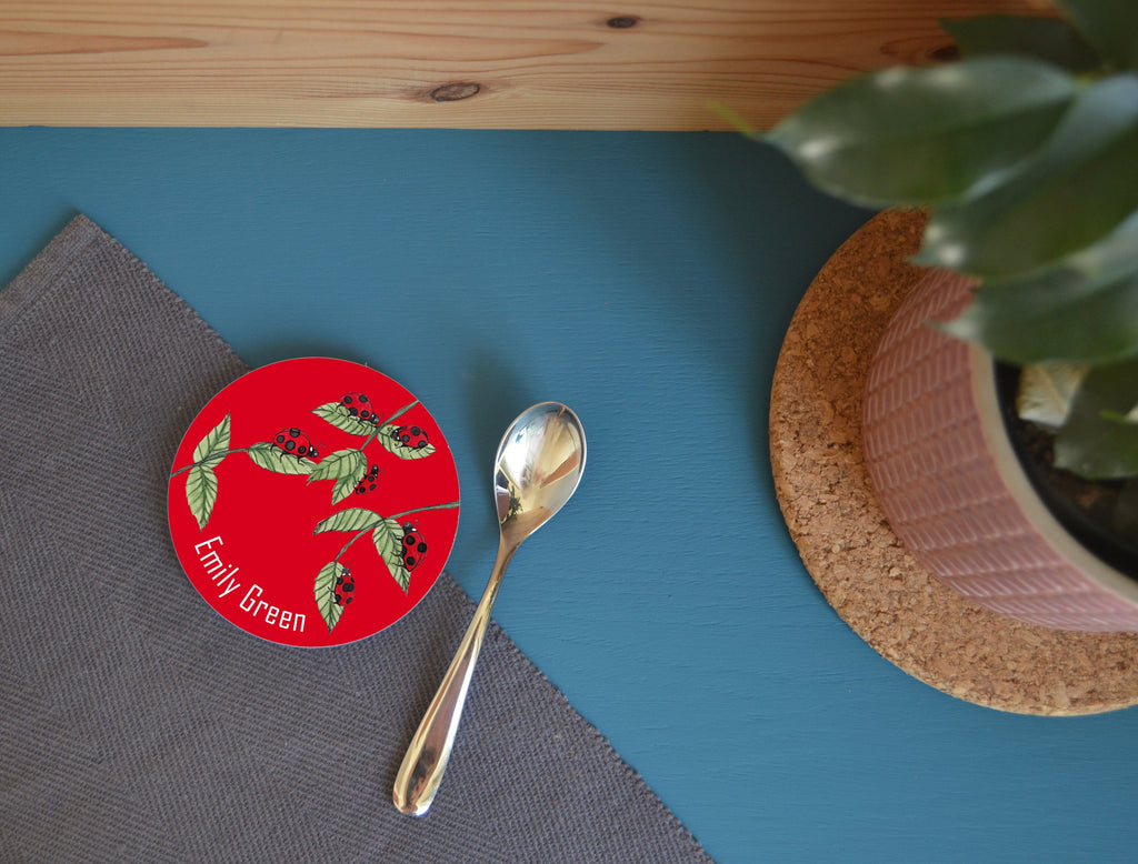 A personalised ladybird coaster on a blue table next to a teaspoon