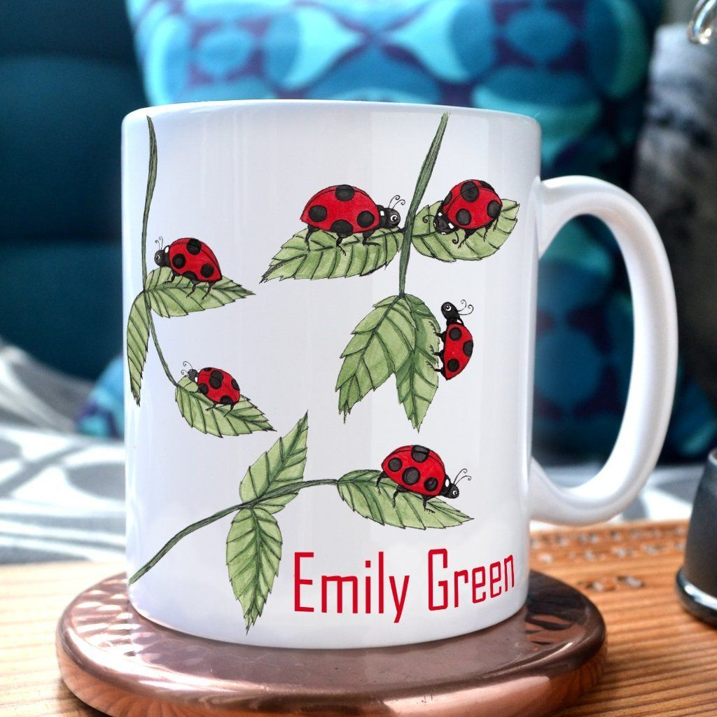 A white mug with a ladybird pattern in red and green. The mug is personalised with a name.
