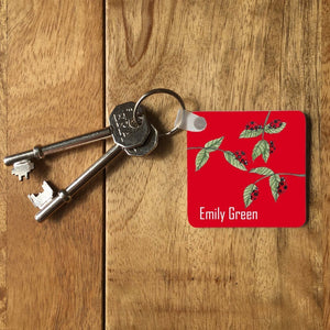 "A personalised square keyring with a ladybird pattern. The keyring includes the name ""Emily Green"". The keyring is on a table with 2 keys attached to it."
