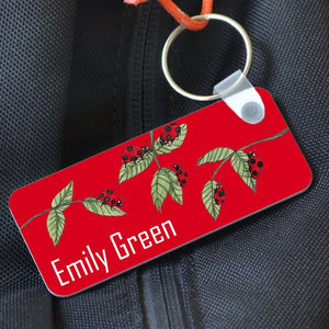 "A rectangular red keyring featuring a ladybird pattern and the name ""Emily Green"". The keyring is attached to a rucksack."