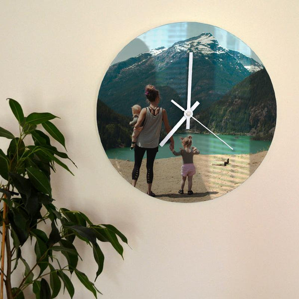 A personalised glass wall clock with a photo of a family printed on it. The clock has white hands and is hanging on a wall.