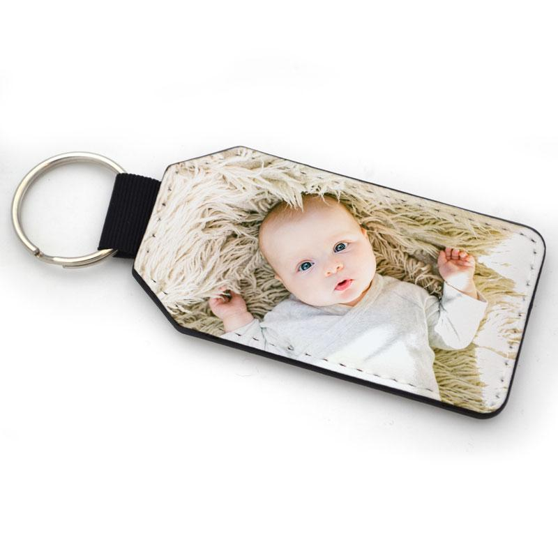 A personalised rectangular leather look keyring with a photo of a baby printed on it