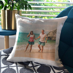 Personalised linen cushion with a family photo printed on it, the cushion is on a blue chair by a house plant.