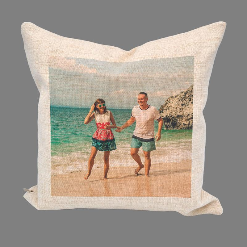 A personalised cream linen cushion with a photo of a man and woman printed on it